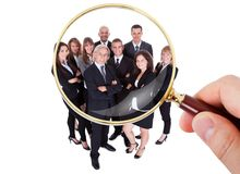 Hand with magnifying glass and group of executives. Person Hand Looking At Group Of Executives Through Magnifying Glass Stock Image