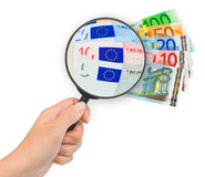 Hand with magnifying glass and money Stock Images