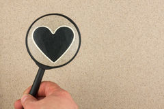 Hand with magnifying glass over the heart in the sand Royalty Free Stock Photo