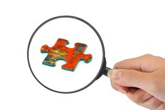 Hand with magnifying glass and puzzle Stock Photo