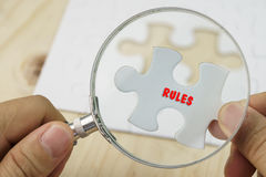 Hand with magnifying glass on puzzle Stock Image