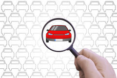 Hand with a magnifying glass searching for a car to rent or buy. Empty copy space for text Royalty Free Stock Photos