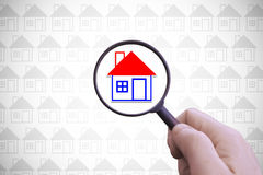 Hand with a magnifying glass searching for a home for rent. Stock Images