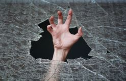 Hand make their way through the broken glass Royalty Free Stock Image