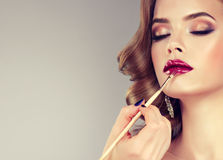 Hand of make-up master, painting lips of model. stock photos