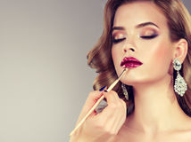 Hand of make-up master is painting lips of young beautiful brunette model. royalty free stock photo