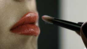 Hand of make-up master, painting lips of young beautiful model. Makeup in progress. stock video
