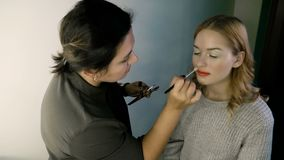 Hand of make-up master, painting lips of young beautiful model. Makeup in progress. stock video footage