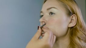Hand of make-up master, painting lips of young beautiful model. Makeup in progress. stock footage
