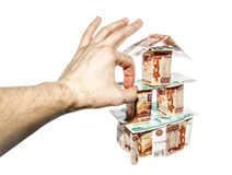 The hand makes a click on House of banknotes. On a white background stock image