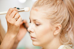 Hand of makeuper applying blush with a brush. Applying make up to a young beautiful model Stock Photo