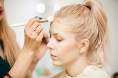 Hand of makeuper applying blush with a brush. Applying make up to a young beautiful model Royalty Free Stock Photo