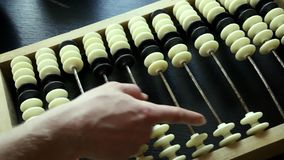 Hand making calculations on vintage abacus sliding beads stock video footage