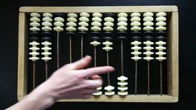 Hand making calculations on vintage abacus sliding beads stock footage