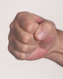 Hand making a fist. Human hand making a fist against a white background Royalty Free Stock Photos