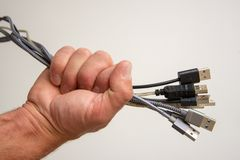 Fist full of cords. Hand making a fist around a bunch of different types of cords stock photos