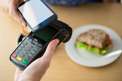 Hand making a payment through NFC technology Royalty Free Stock Image