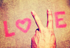 A hand making a peace sign for the letter V in the word love Royalty Free Stock Images