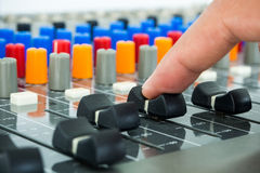 Hand making slide on an audio soundboard. In studio room Stock Image