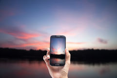 Hand male Asian holding Smartphone taking picture of Twilight ,w. Ith Sea the dawn sun . Overcast Stock Photo