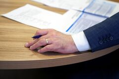 Hand of a male executive holding a fountain pen during a meeting or discussion. Decision making. Filling out documents,