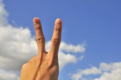 Hand of male showing victory sign. Hand of elderly male showing victory sign with blue sky background Stock Photo