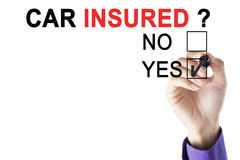 Hand of male worker approving car insured. Hand of male worker using a pen while choosing a yes option with a question of car insured on the whiteboard Stock Image