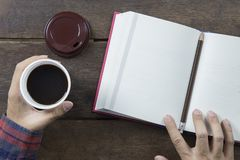 Hand man Asian holding black coffee in white plastic cup and red. Covered opened book blank page with pencil and and brown cap on old wooden table Royalty Free Stock Photo