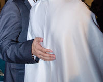 Hand of a man in black jacket hugs bride in white. View from the back Stock Photography