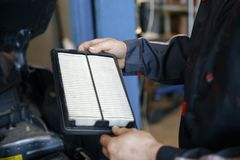 Replacing an air filter in a car stock photo