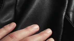 The hand of a man checks to touch the quality of a black natural or artifical leather bag.