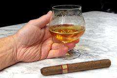 Hand of a man with a cigar and a glass of brandy on the marble table Stock Photos