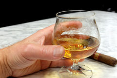 Hand of a man with a cigar and a glass of brandy Stock Photography