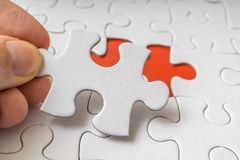 Hand of a man is connecting one last piece of white empty puzzle Stock Photo