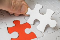 Hand of a man is connecting one last piece of white empty puzzle Stock Image