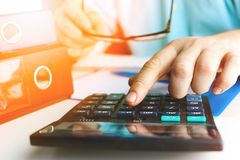 Hand man doing finances and calculate on desk about cost at home office. Toned stock images