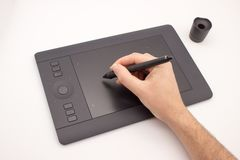 The hand of a man draws a stylus on a graphics tablet. stock photo