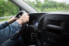 Hand of man driving a car Stock Photos