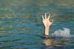 Hand of a man drowning in the sea. Trying to float Stock Photos