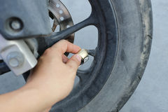 Hand of man fill a wind into the wheels of motorcycle. Royalty Free Stock Images