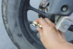 Hand of man fill a wind into the wheels of motorcycle. Stock Images