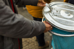 A hand of a man in a grey jacket throwing out trash into a silver and blue trashcan Stock Photo