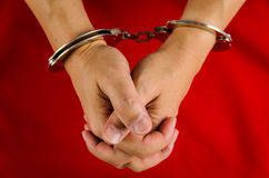 Hand of a man with handcuff. On red background Royalty Free Stock Image