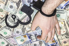 Hand man in handcuffs on the table with money Stock Photography
