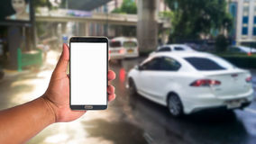 The hand of man hold mobile phone over blurred of traffic jam on Stock Images