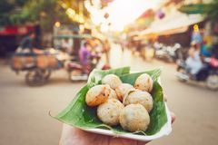 Sweet food on the street market. Hand of man holding bowl with sweet coconut food. Busy street full of restaurants, bars and shops - Siem Reap, Cambodia royalty free stock photo