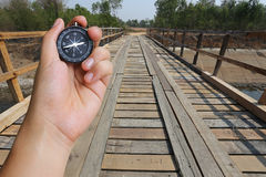 hand of a man holding a compass and wood bridge in the countrysi Royalty Free Stock Photography
