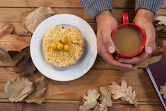 Hand of man holding cup of coffee with breakfast and autumn leaves on table Stock Photos