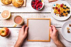 Hand of man holding empty picture frame. Breakfast meal. Stock Photography