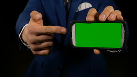 Hand of man holding a green screen smart phone and pointing with finger at display stock footage